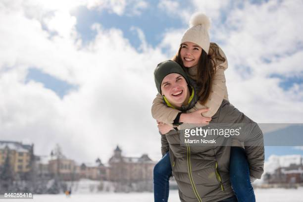 Young guy piggybacking cheerful girlfriend
