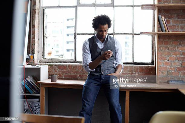 Young guy sitting on desk using smart phone