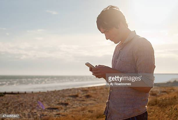 Young guy standing and texting by the sea
