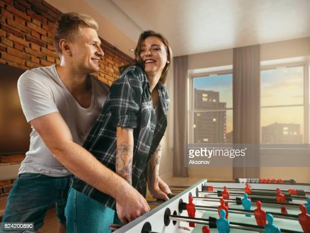 Jeune mec enseigne une fille à jouer le jeu de football/kicker de table