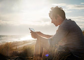 Young guy using tablet computer in sand dunes
