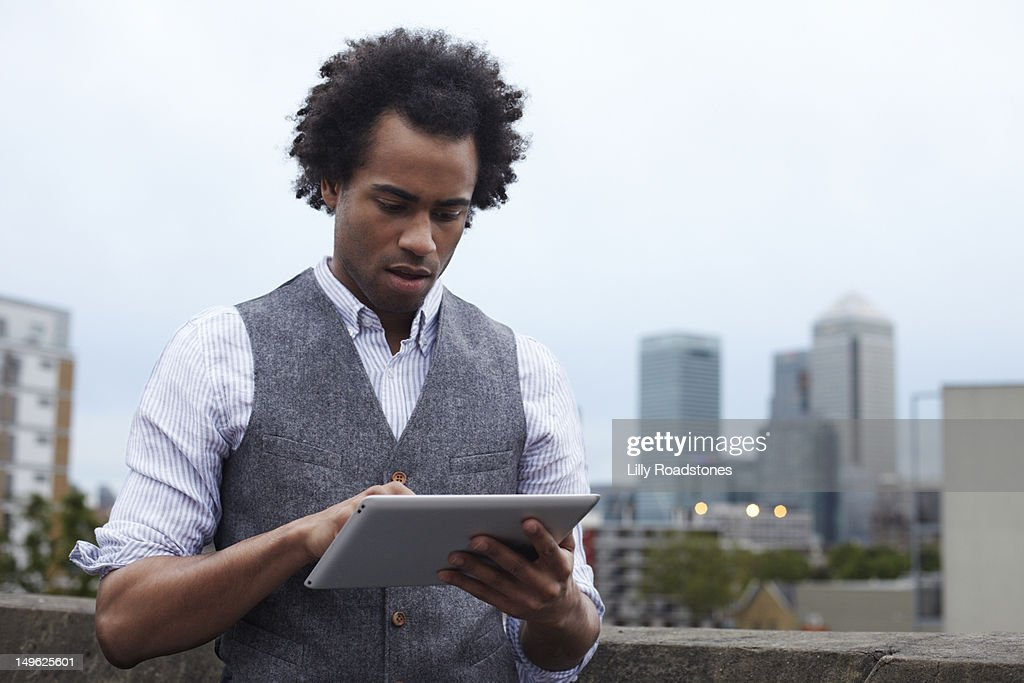 Young guy using tablet computer outside in London