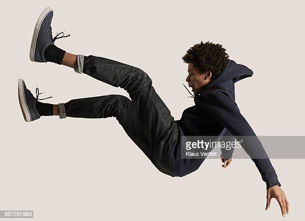 Young guy wearing hoodie, falling in the air