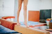 Young gymnast balancing on a balance beam