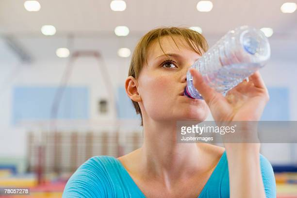 Young gymnast drinking bottled water
