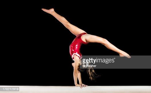 Young gymnast girl exercising on balance beam.