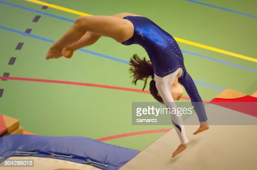 Young gymnast girl performing jump back handspring : Stock Photo