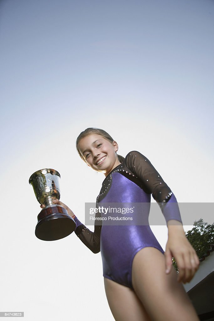 Young gymnast holding trophy : Stock Photo