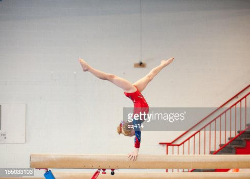 Young Gymnast in Handstand Split on Balance Beam