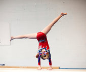 Color image of a level 5 gymnast practicing her beam routine. This image has motion blur and grain.