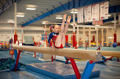 Color image of a 9 year old level 5 gymnast practicing her beam routine. Some grain.