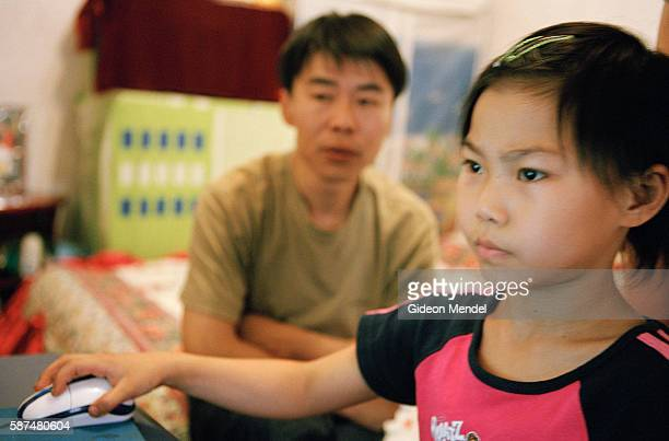 Young gymnast Zhao Chaoyue plays on a computer at home watched by her father Zhao Chunqiang This is during a weekend visit to her family who live in...