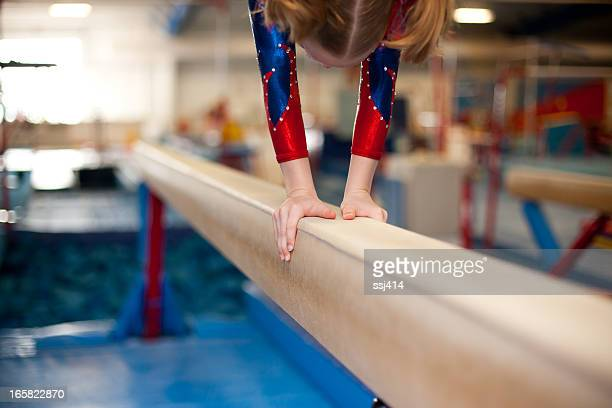 Young Gymnasts Hands on Balance Beam