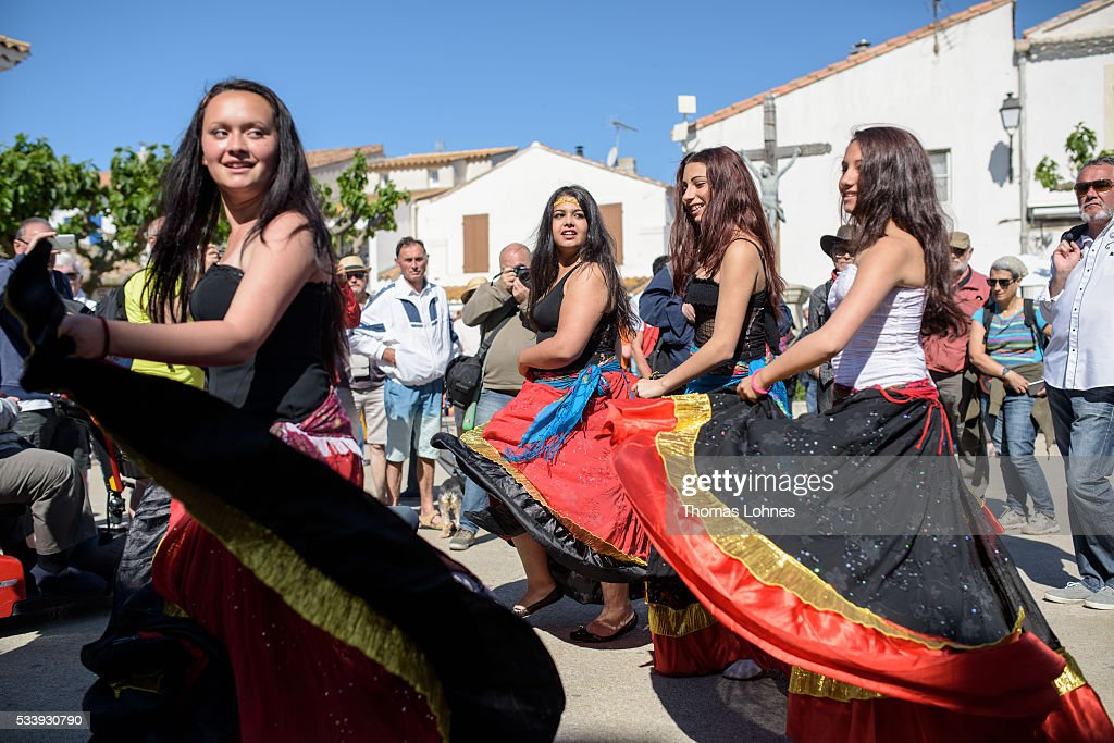 Young Gypsy girls of the Romanies people from Bratislava (Slovakia) dance in front of church on May 24, 2016 in Staintes Maries de la Mere near Arles, France. Gypsies from all over Europe worship 'Sara the Black', their Saint and patroness, for one week. Sara's statue is situated in the crypt of the church. She wears a multicoloured dress and will carried by the gypsies to the sea at this afternoon.