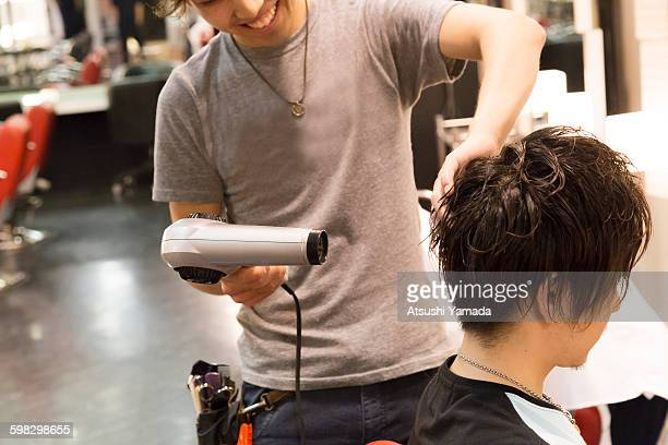 Young hairdresser blowing hair