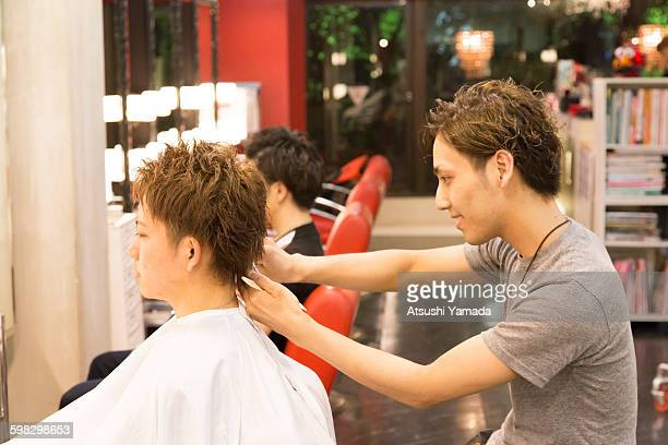 Young hairdresser cutting hair