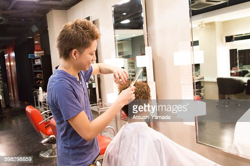 Young hairdresser cutting hair : Stock Photo