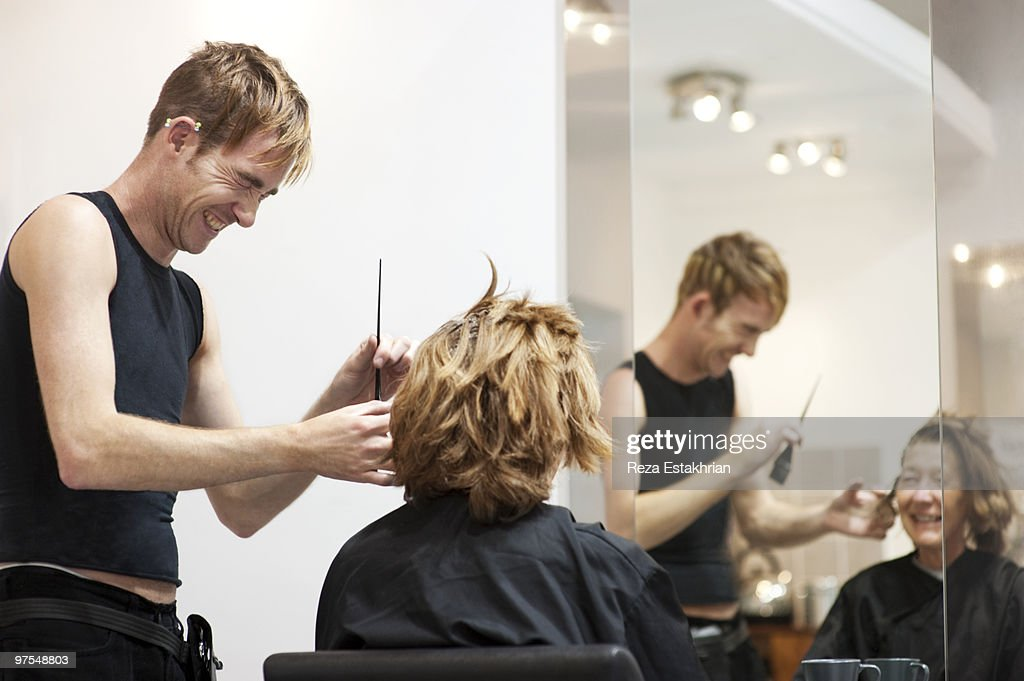 Young hairdresser laughs with customer : Stock Photo