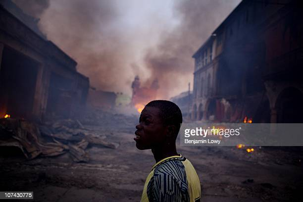 A young Haitian man watches fire consume the remains of several earthquake ravaged warehouses in downtown Port au Prince Haiti On January 12 2010...
