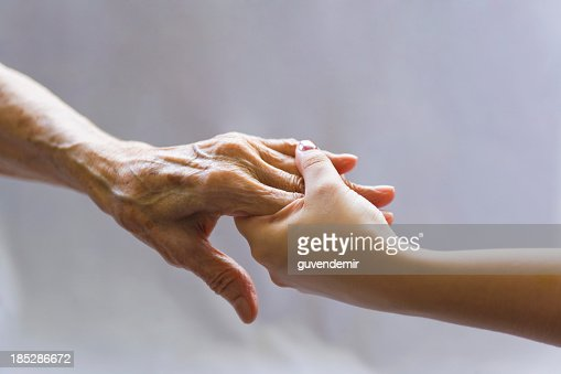 Young hand reaching out to a elderly persons hand