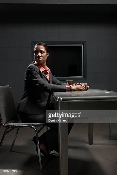Young handcuffed woman sitting at desk in interrogation room, looking away
