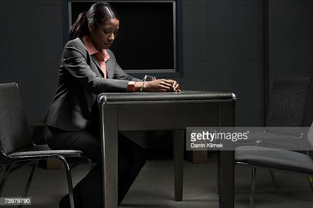 Young handcuffed woman sitting at table in interrogation room, side view