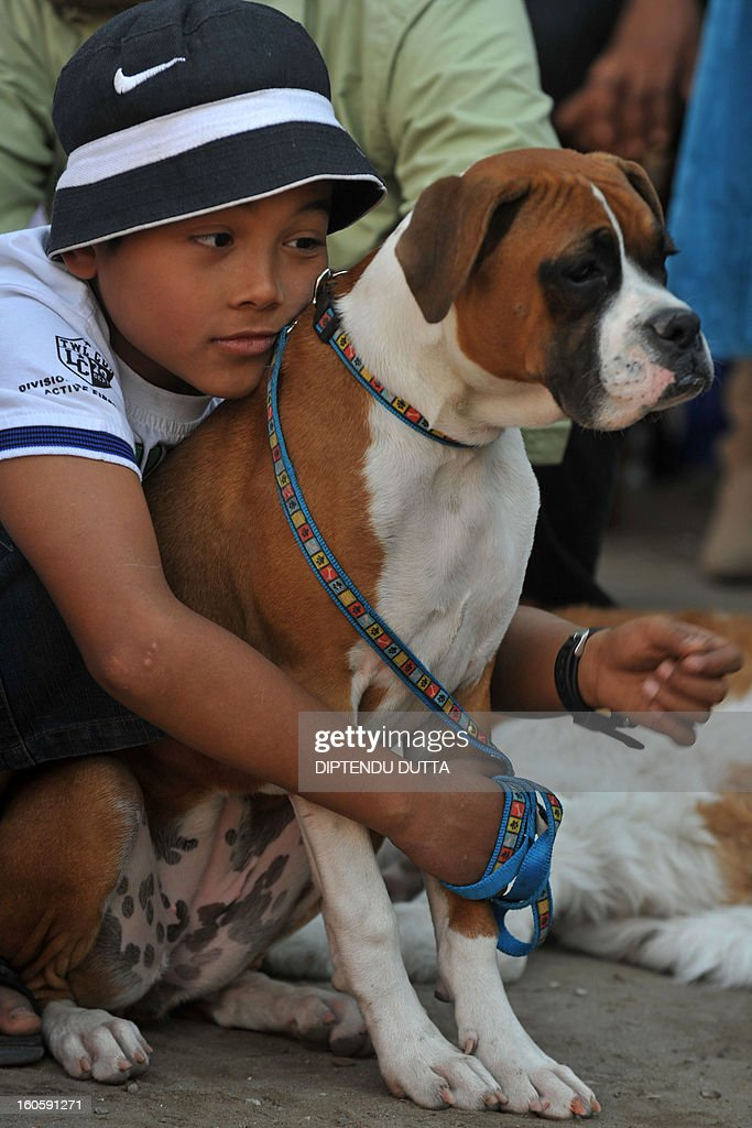 A young handler hugs his pet during a dog show in Siliguri on February 3, 2013. The event which took place in the eastern Indian city was organised by the People for animals (PFA). AFP PHOTO/Diptendu DUTTA