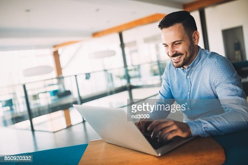 Young handsome architect working on laptop in office : Stock Photo
