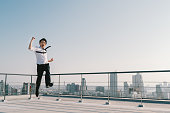 Young handsome Asian businessman jumping high, celebrate success winning pose on building rooftop. Work, job, or successful business concept. Cityscape background with copy space on sunny blue sky