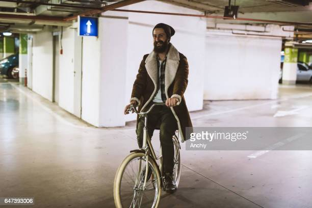 Young handsome bearded hipster in warm clothes riding a bicycle