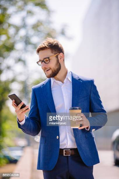 Young handsome businessman typing message