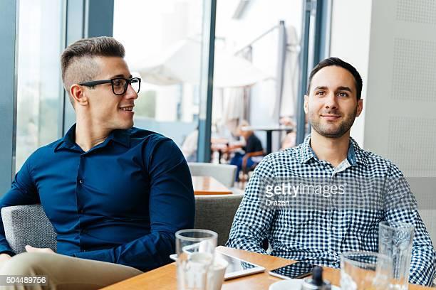 Junge gut aussehend lässig Männer trinken Kaffee und sprechen im Café