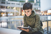 young handsome caucasian brown straight hair woman sitting in city dusk, holding tablet, looking downward screen, face illuminated by screen light - technology, social network, communication concept