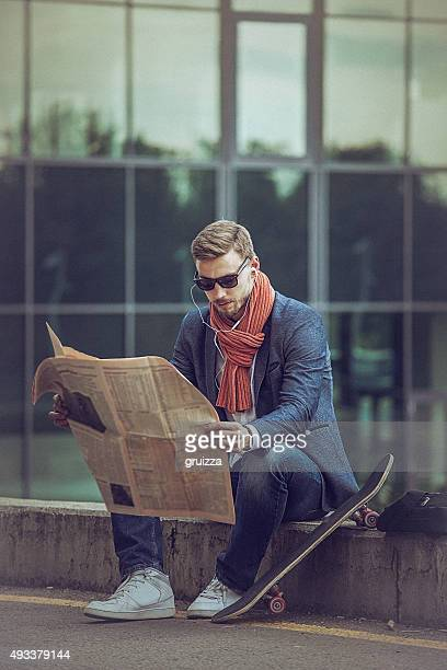 Young handsome entrepreneur reading newspaper in the urban envir