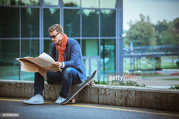 Young handsome entrepreneur reading newspaper in the urban environment