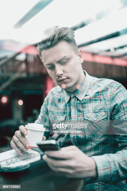 Young Handsome Male Drinking First Morning Coffee in a Cafe and Reading His To Do List