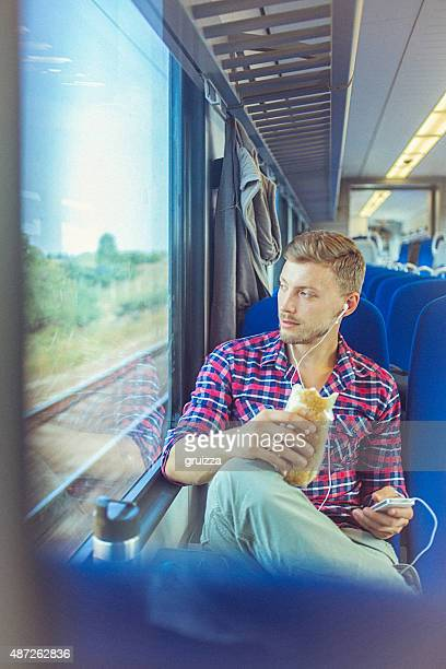 Young handsome man at train using smartphone and eating sandwich