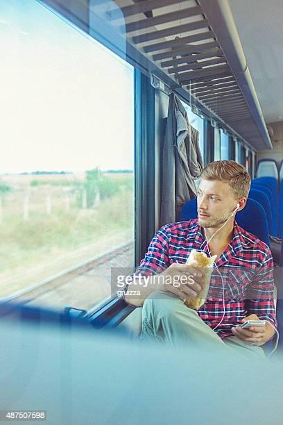 Jeune bel homme à l'aide de smartphone et de train de manger un sandwich