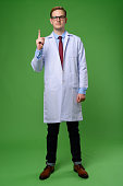 Studio shot of young handsome man doctor wearing eyeglasses against green background