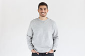 Young handsome man in oversized sweatshirt, standing isolated on gray background
