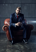 Young handsome businessman with beard in black suit sitting on chair and looking on camera