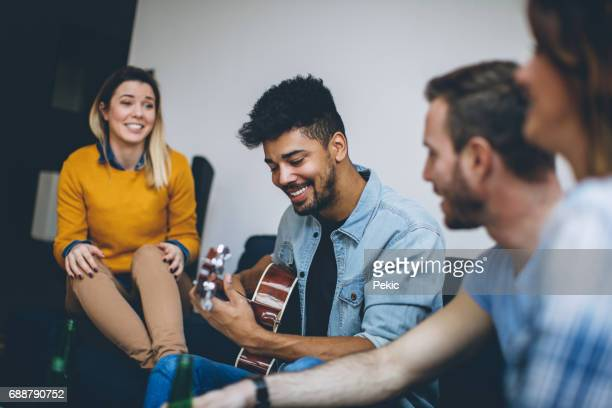 Young handsome man playing guitar to his friends