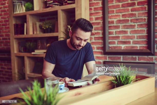 Young Handsome Man Reading Book in a Modern Cafe Restaurant
