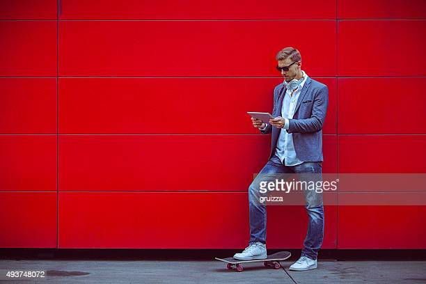 Young handsome man using digital tablet beside red wall.