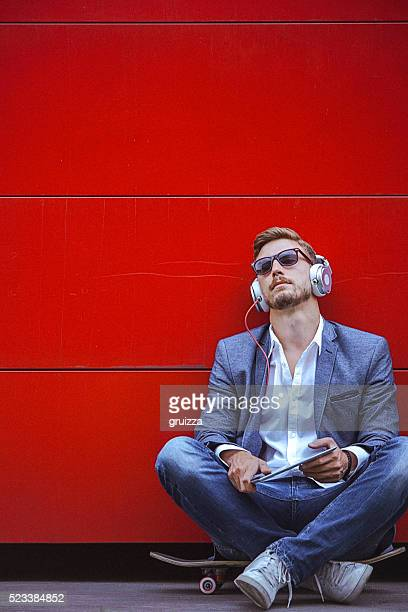 Young handsome man using digital tablet beside the red wall