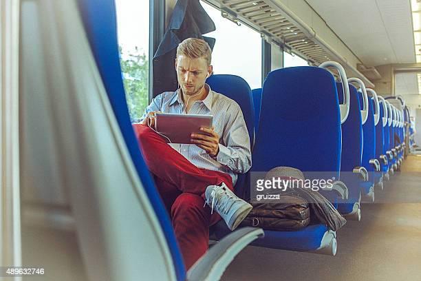 Junger gut aussehender Mann mit tablet PC während die Fahrt zur Arbeit