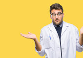 Young handsome man wearing doctor, scientis coat over isolated background clueless and confused expression with arms and hands raised. Doubt concept.