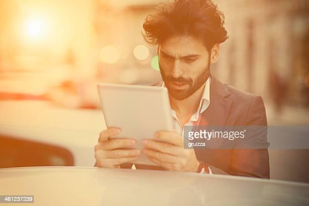Jeune bel homme avec barbe, à l'aide de tablette numérique à l'extérieur