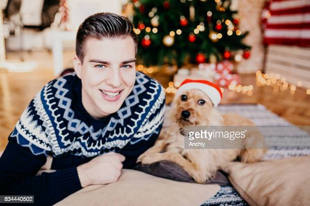Young handsome man with his dog posing in front of a Christmas tree