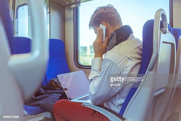 Junger gut aussehender Mann Arbeiten auf dem laptop während die Fahrt zur Arbeit